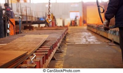 A man working with a lifting crane with a hook on the end....