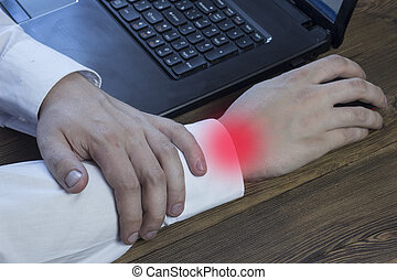 A man works at a computer and holds his hand, his arm hurts, tunnel syndrome