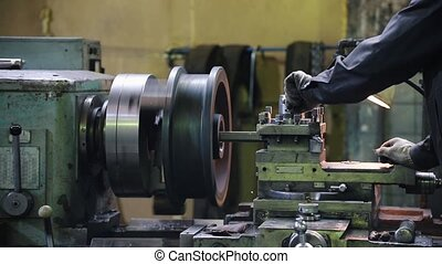 A man works with a lathe. Routes material to the turning...