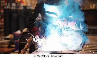 A man works with a welding machine and using a torch - Mid...