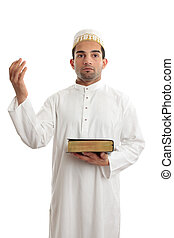 A man worshipping - A man holding a holy book such as a...