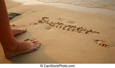 A man writes a word in the sand, summer vacation concept