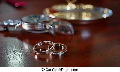 A man's and woman's wedding rings . A man's wrist watch is...