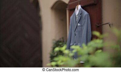 A man's gray jacket suit hanging in the yard hangs on a hanger before the groom's wedding