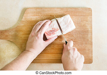 A man's hand cuts the pieces of fat