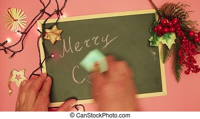 A man's hand erases Merry Christmas on a black board and writes the end.