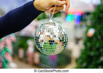 man's hand holds a Christmas tree toy disco ball, a holiday decoration