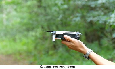 A man's hand holds a drone or quadrocopter against the...