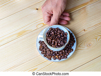 A man's hand holds a white mug with coffee beans on a wooden background