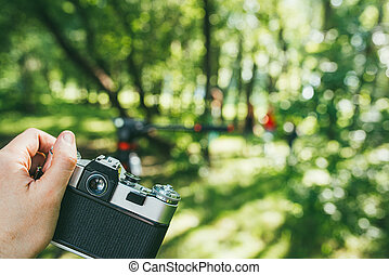 a man's hand holds an old vintage film camera and photographs a green landscape. first-person view POV