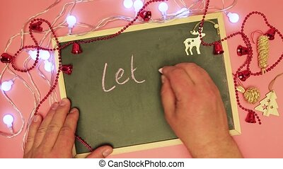 A man's hand is writing let it show on the black board.