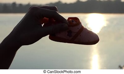 a Man's Hand Plays With Baby's Slippers on a Lake Bank at...