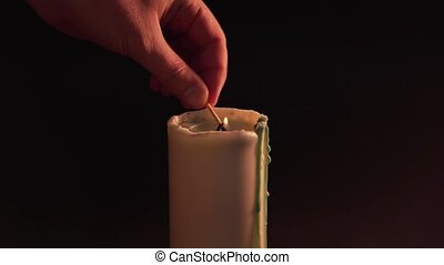 A man's hand sets fire to a candle on a black background with a match. Isolate, static shot. The concept of witchcraft, divination and magic 4k