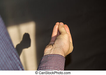 man's hand with fingers folded in a pinch, a shadow on the wall by hand
