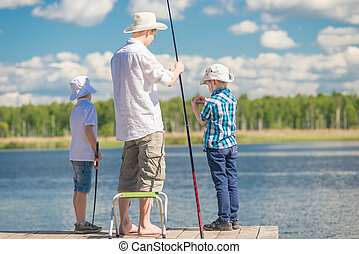 a man's hobby - a father with his sons on fishing in good weather on the lake