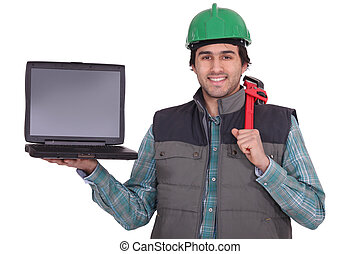 A manual worker holding a laptop