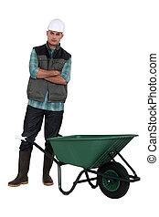 A manual worker standing by a wheelbarrow.