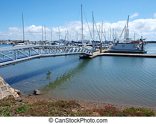 A marina with boats and white cloud in blue sky.