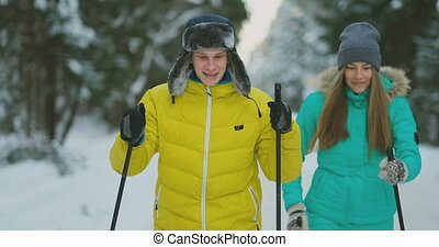 A married couple is skiing in the forest practicing a...
