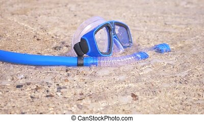 a mask and snorkel on the beach near the sea, slow motion.
