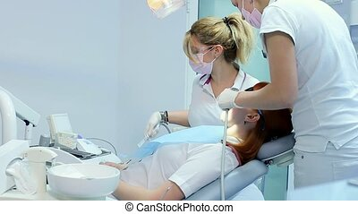 A Masked and Gloved Dentist Explains the Upcoming Treatment...
