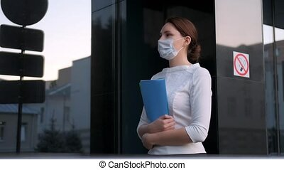 A masked business girl walks next to the company building. Work during an epidemic in quarantine. Medical protection and health