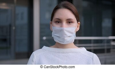 masked business woman walks next to the company building. Work during an epidemic in quarantine. Medical protection and health