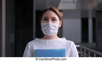 masked business woman walks next to the company building. Work during epidemic