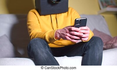 A masked man at a carnival party uses a smartphone to write a message.