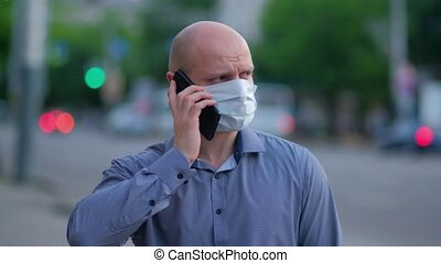 masked man dials a number and talks on the phone