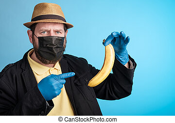 a masked man holds a banana in one hand, points at it with the other