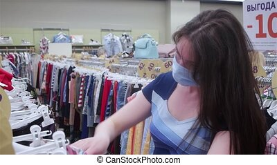 masked woman chooses clothes in a store during quarantine