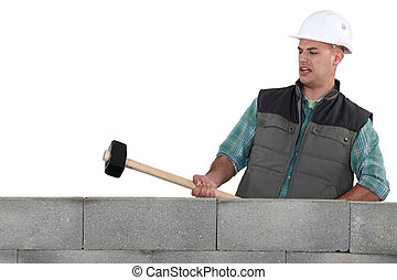 A mason about to destroy a wall with a sledgehammer.