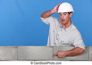 A mason pointing at a wall.