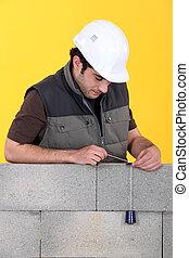 A mason using a plumb bob to check his wall.