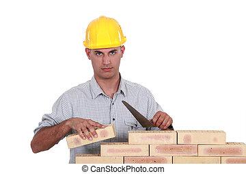 A mason working on a wall.