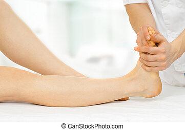 massage - a massage therapist massaging slender woman's legs
