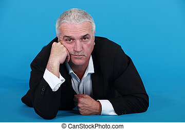 A mature bored businessman laying on the floor.