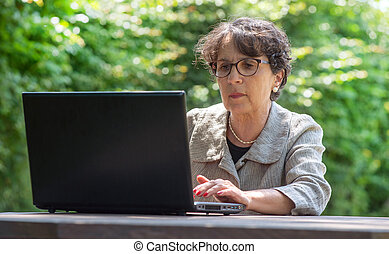 mature brunette using laptop in the garden