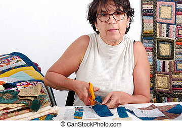 mature brunette woman cutting fabric for sewing patchwork
