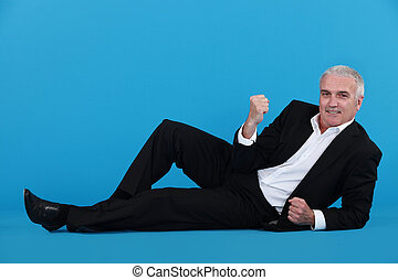 A mature businessman laying on the floor gesturing a yes sign.