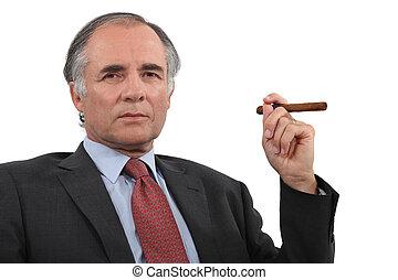 A mature businessman smoking a cigar.