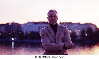 A mature businessman standing on a bridge in Prague at dusk....