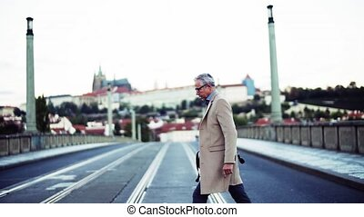 A mature businessman with bag crossing a road in Prague...