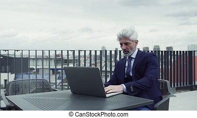 A mature businessman with laptop sitting on a terrace,...