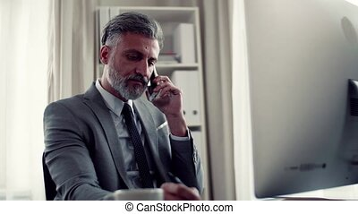 A mature businessman with smartphone making a phone call.