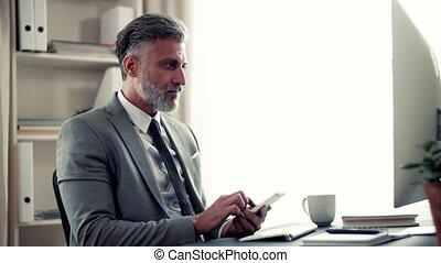 A mature businessman with smartphone sitting at the table,...