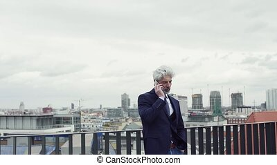 A mature businessman with smartphone standing on a terrace,...