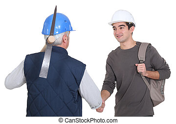 A mature construction worker shaking hands with his trainee.