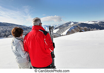 a mature couple in front of a beautiful snowy landscape